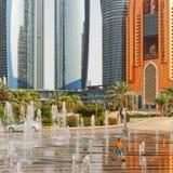 Kleiner Junge, der in den Brunnen vor Abu Dhabi &#x27 spielt; Hoch-Aufstiege s Corniche Stockbilder