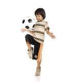Kleiner Junge, der den Fußball lokalisiert spielt Lizenzfreie Stockfotos