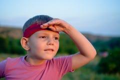 Kleiner Junge, der in den Sonnenuntergang blickt Lizenzfreies Stockbild