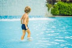Kleiner Junge, der den Spaß läuft im Swimmingpool hat stockbild