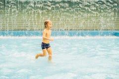 Kleiner Junge, der den Spaß läuft im Swimmingpool hat stockfoto