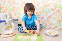 Kleiner Junge, der den Teig zu Hause sitzt auf einer Küche der Tabelle flachdrückt Lizenzfreies Stockfoto