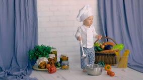 Kleiner Junge, der in der Küchendekoration sitzt und mit Gemüse kocht stock video footage