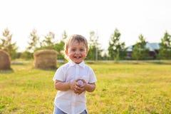 Kleiner Junge, der in der Natur spielt Stockbild