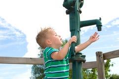 Kleiner Junge, der an der Pumpe spielt Lizenzfreies Stockfoto