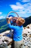Kleiner Junge, der die Berge durch Teleskop betrachtet Stockfotografie