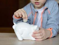 Kleiner Junge, der die 1 Euromünze setzt Stockbilder