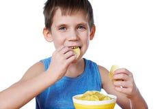 Kleiner Junge, der die Kartoffelchips lokalisiert isst Stockfotos