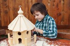 Kleiner Junge, der die letzten letzten Schliffe auf einem Vogelhaus macht Lizenzfreies Stockbild