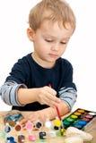 Kleiner Junge, der die Steine mit Aquarell malt stockbilder