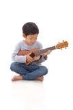 Kleiner Junge, der die Ukulele spielt stockfoto