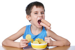 Kleiner Junge, der die Würste und Kartoffelchips lokalisiert isst Stockfotografie