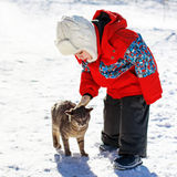 Kleiner Junge, der draußen mit Katze im Winter spielt lizenzfreies stockfoto