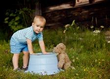 Kleiner Junge, der draußen mit seinem Teddybären spielt Lizenzfreies Stockbild
