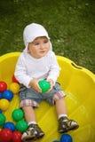 Kleiner Junge, der draußen mit Spielwaren spielt. Lizenzfreie Stockfotos