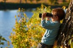 Kleiner Junge, der durch binokulares schaut Lizenzfreies Stockbild