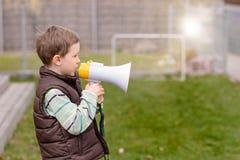 Kleiner Junge, der durch ein Megaphon schreit Stockbild