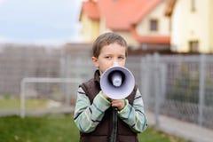 Kleiner Junge, der durch ein Megaphon schreit Stockfotografie