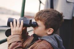 Kleiner Junge, der durch Ferngläser während der Reise schaut lizenzfreie stockbilder