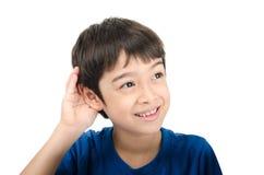 Kleiner Junge, der eigenhändig bis zum Ohr auf weißem Hintergrund lissening ist Stockfotografie