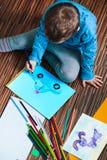 Kleiner Junge, der ein buntes Bild eines Autos unter Verwendung des Bleistifts cray zeichnet Stockfotografie