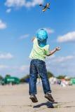 Kleiner Junge, der ein Flugzeugmodell beim Springen startet Lizenzfreies Stockfoto