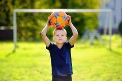 Kleiner Junge, der ein Fußballspiel am Sommertag spielt Stockfoto