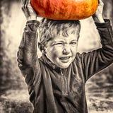 Kleiner Junge, der ein Gesicht mit schwerem Kürbishut macht Lizenzfreies Stockfoto