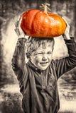 Kleiner Junge, der ein Gesicht mit schwerem orange Kürbishut macht Stockfoto