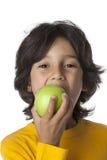 Kleiner Junge, der ein grünes aplle isst stockfoto