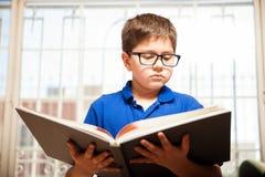 Kleiner Junge, der ein großes Buch liest Lizenzfreies Stockbild