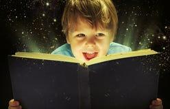 Kleiner Junge, der ein magisches Buch trägt lizenzfreie stockfotografie