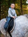 Kleiner Junge, der ein Pferd reitet Lizenzfreie Stockfotografie