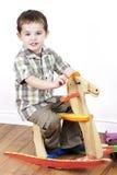 Kleiner Junge, der ein Schwingpferd reitet Stockbild