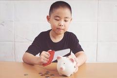 Kleiner Junge, der ein Sparschwein bricht Stockfotografie