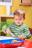 Kleiner Junge, der eine Abbildung im Kindergarten zeichnet Stockfoto