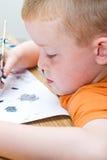 Kleiner Junge, der eine Abbildung malt Stockbild