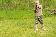 Kleiner Junge, der eine automatische Waffe zeigt Stockbilder