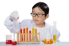 Kleiner Junge, der eine Chemikerflüssigkeit auf Studio mischt Stockfoto