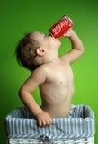 Kleiner Junge, der eine Coca Cola trinkt Lizenzfreie Stockfotografie