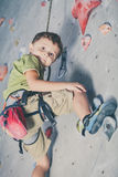 Kleiner Junge, der eine Felsenwand klettert Lizenzfreie Stockfotografie