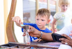 Kleiner Junge, der eine Glasflasche mit Pigmenten füllt lizenzfreies stockfoto