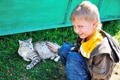 Kleiner Junge, der eine Katze streicht Stockfotografie
