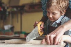 Kleiner Junge, der eine Planke sägt stockfoto