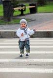 Kleiner Junge, der eine Straße kreuzt Lizenzfreies Stockbild