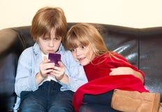 Kleiner Junge, der eine Textnachricht auf einem Smartphone liest lizenzfreie stockbilder
