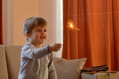 Kleiner Junge, der eine Wunderkerze hält stockfotografie