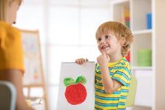 Kleiner Junge, der eine Zeichnung für Mama anhält Lizenzfreie Stockbilder