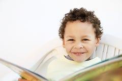 Kleiner Junge, der eine Zeitung liest lizenzfreie stockfotos