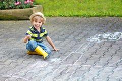 Kleiner Junge, der eine Zugmaschine mit Kreide im Sommer malt Stockfotografie